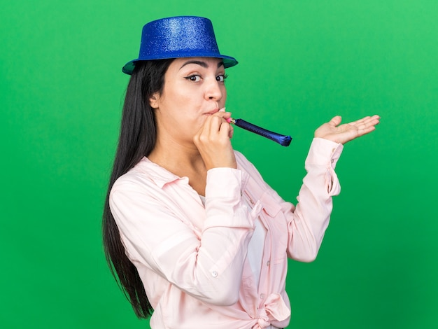 Tevreden jonge mooie vrouw met feestmuts die feestfluitje blaast en hand geïsoleerd op groene muur verspreidt