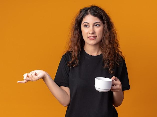 Tevreden jonge mooie vrouw met kopje thee kijkend en wijzend naar kant geïsoleerd op oranje muur orange