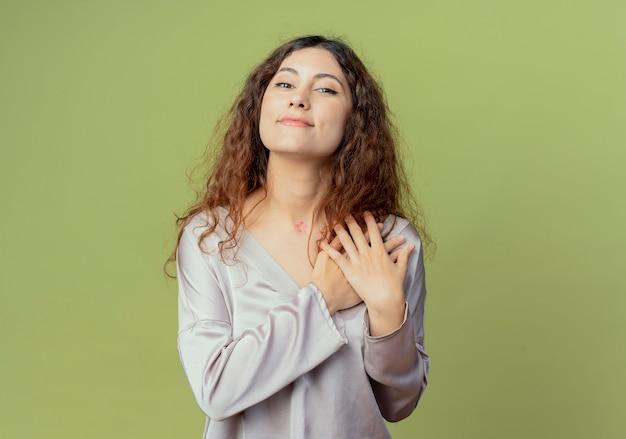 Tevreden jonge mooie vrouwelijke beambte die handen op schouder zet die op olijfgroen wordt geïsoleerd