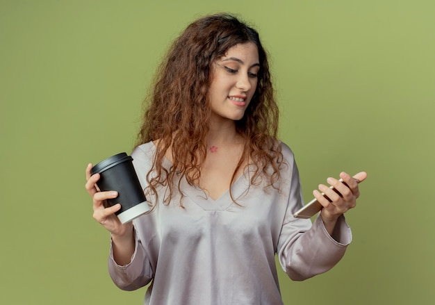 Tevreden jonge mooie vrouwelijke beambte die kop van koffie houdt en telefoon in haar hand bekijkt die op olijfgroene muur wordt geïsoleerd