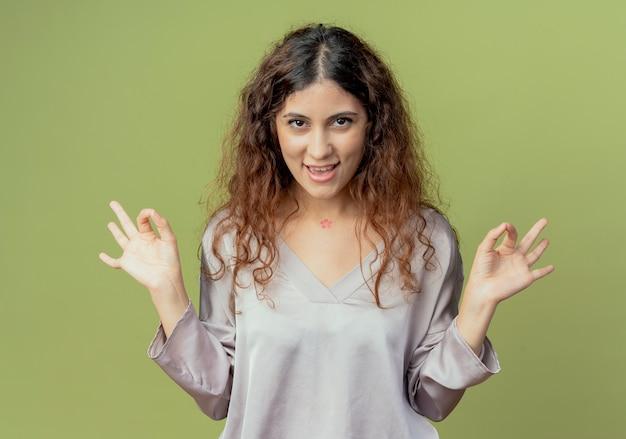 Tevreden jonge mooie vrouwelijke beambte die okgebaar toont dat op olijfgroene muur wordt geïsoleerd
