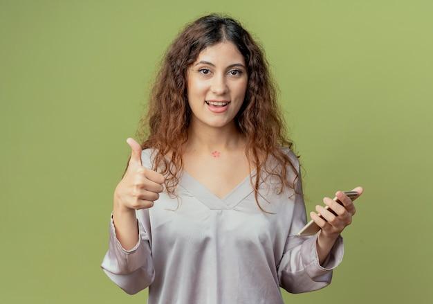 Tevreden jonge mooie vrouwelijke kantoormedewerker met telefoon en haar duim omhoog geïsoleerd op olijfgroene muur