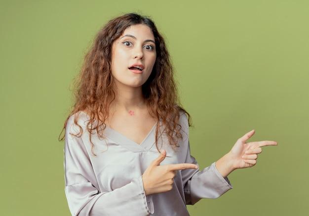 Tevreden jonge mooie vrouwelijke kantoormedewerker wijst naar kant geïsoleerd op olijfgroene muur met kopie ruimte