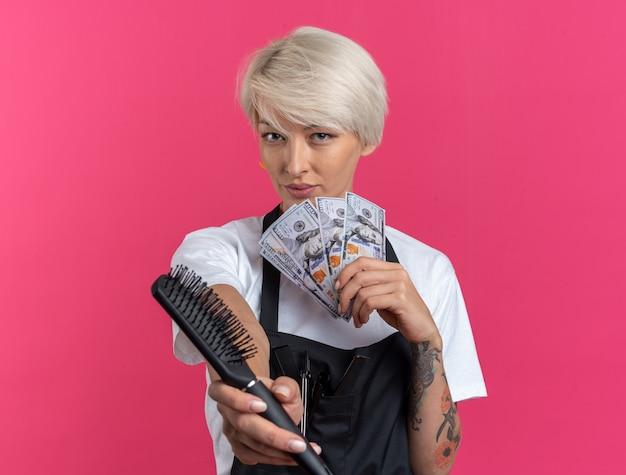 Tevreden jonge mooie vrouwelijke kapper in uniform die kam uitsteekt met contant geld geïsoleerd op roze muur