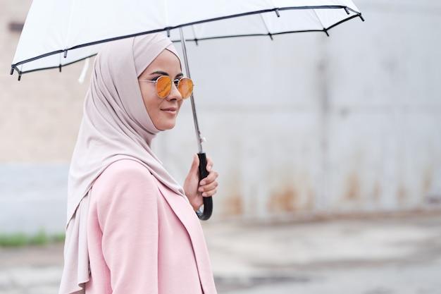 Tevreden jonge moslimvrouw in roze hijab die paraplu en zonnebril gebruikt als bescherming tegen de zon terwijl ze alleen loopt of op vriend wacht