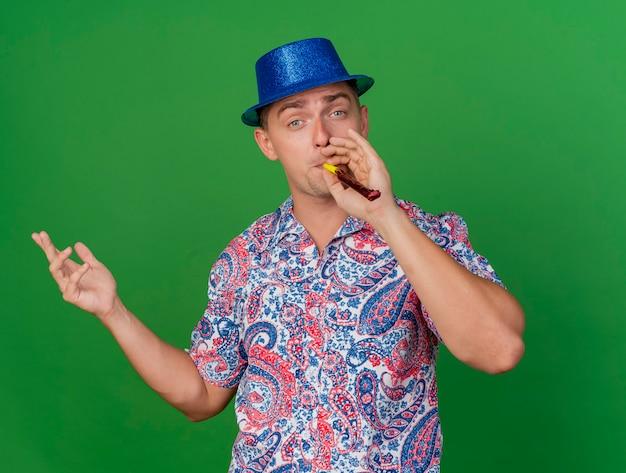 Tevreden jonge partij kerel die blauwe hoed draagt ?? blazende partijventilator en spreidende hand die op groen wordt geïsoleerd