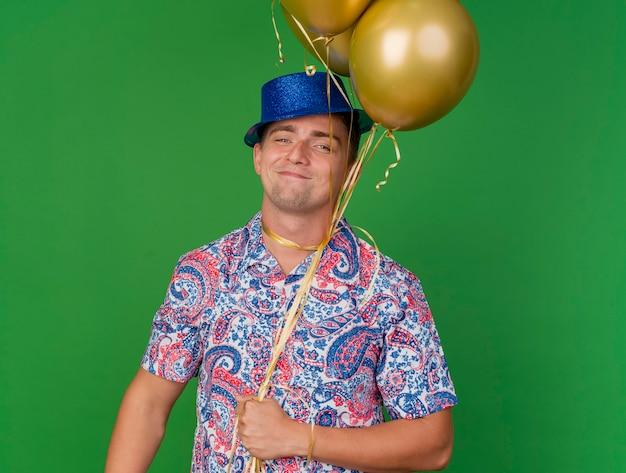 Tevreden jonge partij kerel die blauwe hoed draagt die ballons houdt die om hals worden gebonden die op groen wordt geïsoleerd