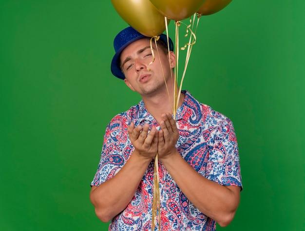 Tevreden jonge partij kerel die blauwe hoed draagt die ballons houdt en kusgebaar toont dat op groen wordt geïsoleerd