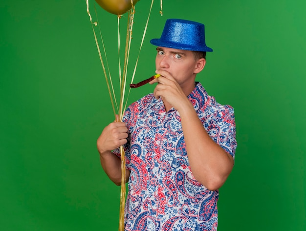 Tevreden jonge partij kerel die blauwe hoed draagt die ballons houdt en partijventilator blaast die op groen wordt geïsoleerd