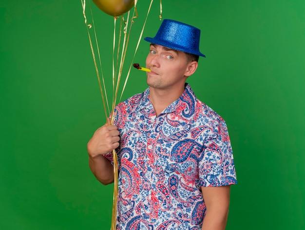 Tevreden jonge partij kerel die blauwe hoed draagt die ballons houdt en partijventilator in mond zet die op groen wordt geïsoleerd