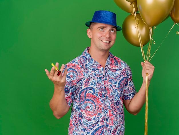 Tevreden jonge partij kerel die blauwe hoed draagt die ballons met partijblazer houdt die op groene achtergrond worden geïsoleerd