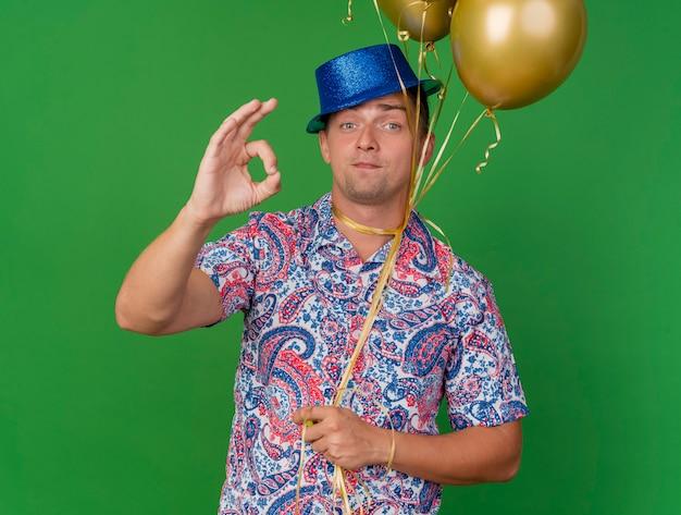 Tevreden jonge partij kerel die blauwe hoed draagt die ballons om hals houdt vastgebonden die goed gebaar tonen dat op groene achtergrond wordt geïsoleerd