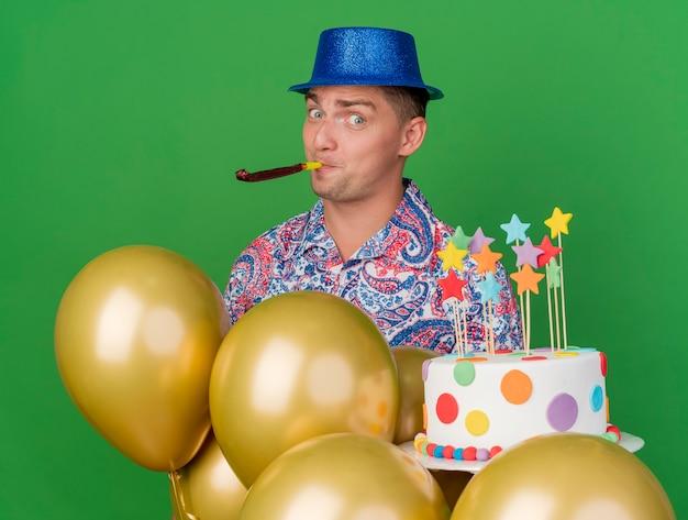Tevreden jonge partij kerel die blauwe hoed draagt die cake blaast partijventilator die zich achter ballons bevindt die op groen worden geïsoleerd