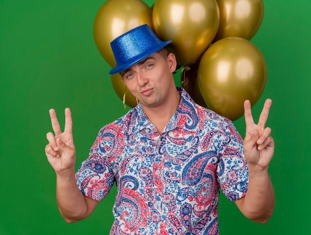 Tevreden jonge partij kerel die blauwe hoed draagt die zich voor ballons bevindt die vredesgebaar tonen dat op groene achtergrond wordt geïsoleerd