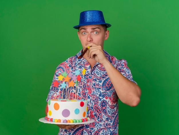 Tevreden jonge partij kerel die de blauwe cake van de hoedholding draagt en die partijventilator blaast op groen wordt geïsoleerd
