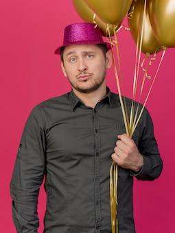 Tevreden jonge partij kerel die roze hoed draagt die ballons houdt die op roze worden geïsoleerd
