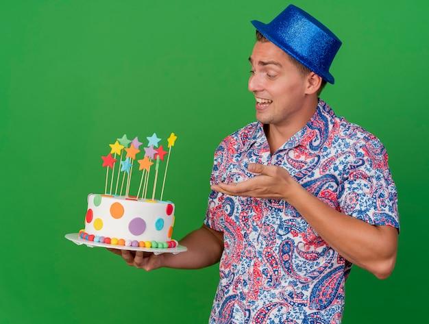 Tevreden jonge partijkerel die blauwe hoedenholding draagt en met hand wijst op cake die op groen wordt geïsoleerd