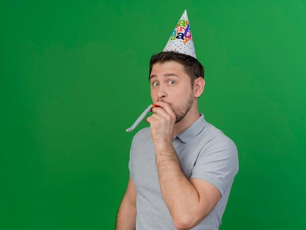 Tevreden jonge partijkerel die de blazende partijventilator van de verjaardagskap draagt die op groen wordt geïsoleerd