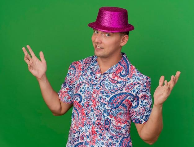 Tevreden jonge partijkerel die roze hoed draagt die handen uitspreidt die op groen worden geïsoleerd