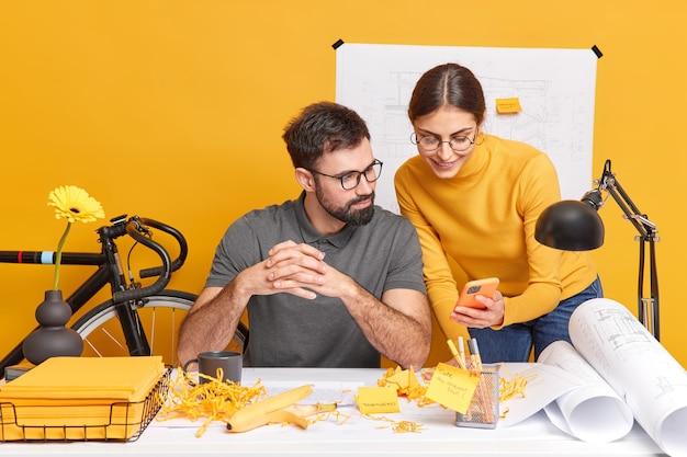 Tevreden jonge professionele vrouw en man kantoormedewerkers werken samen tijdens teamwork op blauwdrukken zoeken naar ideeën op internet geconcentreerd op moderne mobiele telefoon bespreken ideeën voor project