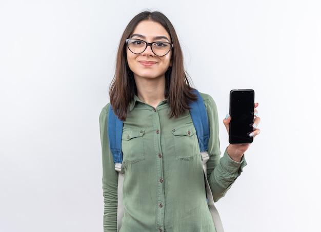 Tevreden jonge schoolvrouw die een bril draagt met een rugzak met telefoon