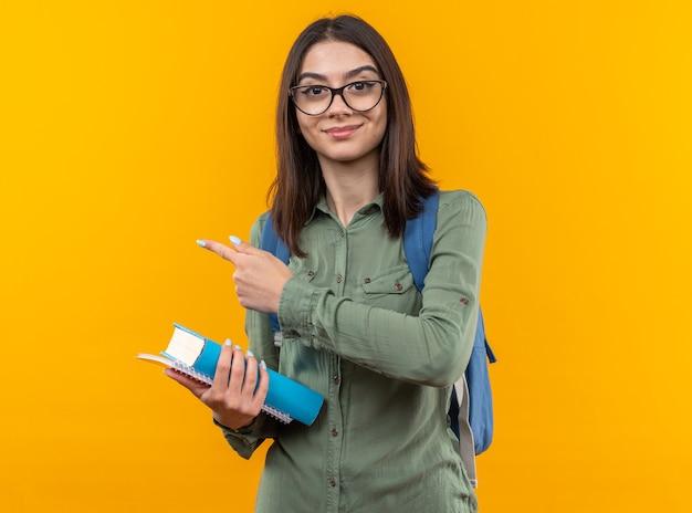 Tevreden jonge schoolvrouw die een rugzak draagt met een bril die boeken aan de zijkant vasthoudt