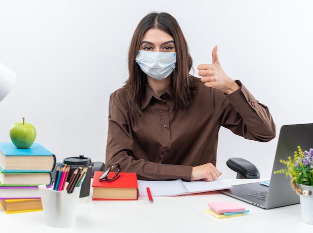 Tevreden jonge schoolvrouw met een medisch masker zit aan tafel met schoolgereedschap met duim omhoog