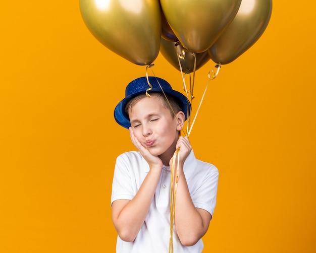 Tevreden jonge slavische jongen met blauwe feestmuts die hand op het gezicht legt en heliumballonnen vasthoudt die op een oranje muur met kopieerruimte worden geïsoleerd