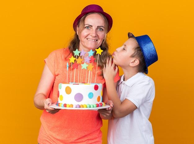 Tevreden jonge slavische jongen met blauwe feestmuts die zijn moeder probeert te kussen met een paarse feestmuts en een verjaardagstaart vasthoudt op een oranje muur met kopieerruimte