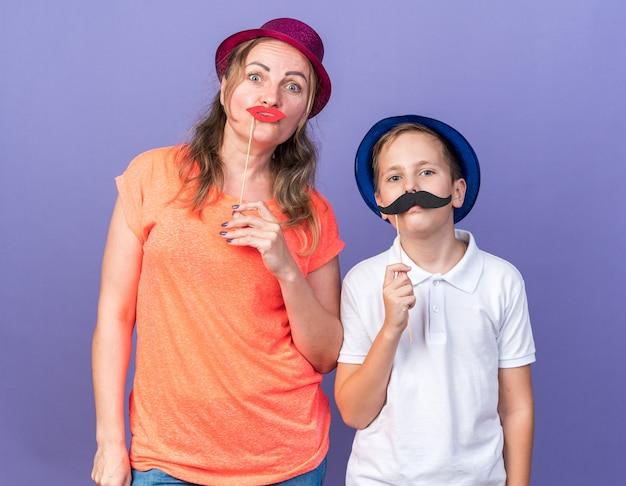 Tevreden jonge slavische jongen met blauwe feestmuts met valse snor op stok staande met zijn moeder met paarse feesthoed en valse lippen op stok op paarse muur