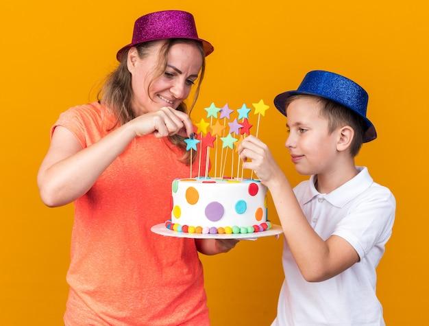 Tevreden jonge slavische jongen met blauwe feestmuts met verjaardagstaart met zijn moeder met paarse feestmuts geïsoleerd op oranje muur met kopieerruimte