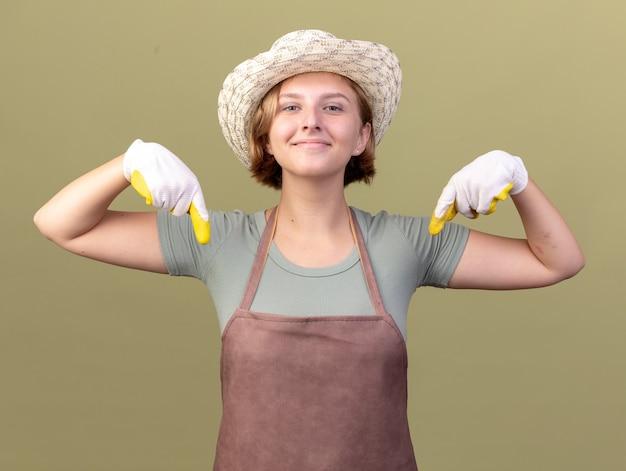 Tevreden jonge slavische vrouwelijke tuinman die het tuinieren hoed en handschoenen draagt die naar beneden op olijfgroen wijzen
