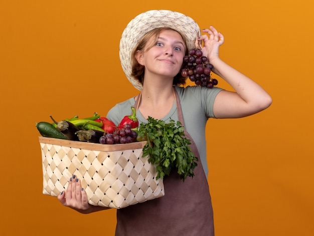 Tevreden jonge slavische vrouwelijke tuinman die tuinieren hoed draagt die plantaardige mand en druiven op sinaasappel houdt