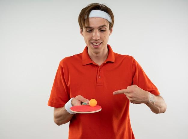Tevreden jonge sportieve kerel die hoofdband met polsbandholding draagt en naar pingpongracket met bal wijst die op witte muur wordt geïsoleerd