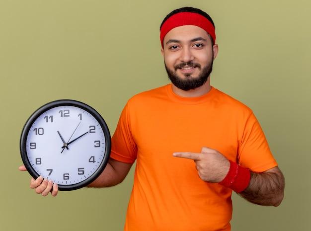 Tevreden jonge sportieve man met hoofdband en polsbandje bedrijf en wijst op muurklok geïsoleerd op olijfgroene achtergrond
