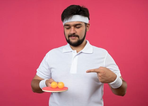 Tevreden jonge sportieve man met hoofdband en polsbandje houden en wijst op pingpongracket met ballen