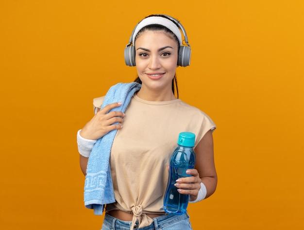 Tevreden jonge sportieve vrouw die hoofdband en polsbandjes draagt die hoofdtelefoons dragen die waterfles met handdoek op schouder houden die voorste grijpende handdoek bekijken die op oranje muur wordt geïsoleerd
