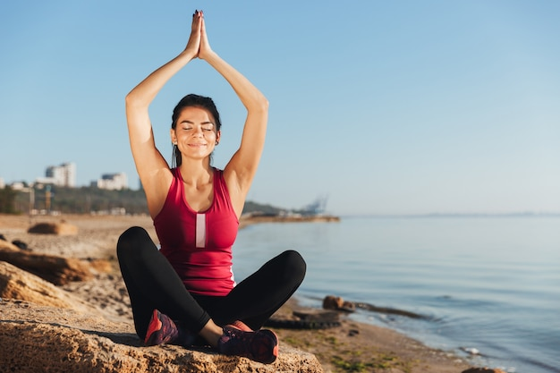 Tevreden jonge sportvrouwenzitting in yogapositie
