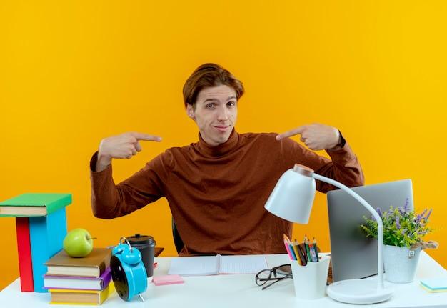 Tevreden jonge student jongen zit aan bureau met school tools wijst naar zichzelf