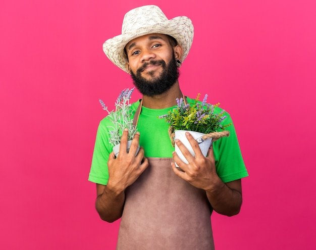 Tevreden jonge tuinman afro-amerikaanse man met een tuinhoed met bloemen in een bloempot