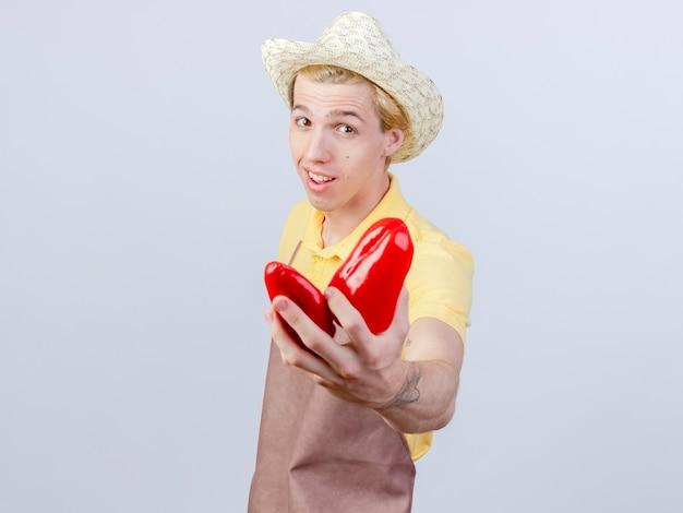 Tevreden jonge tuinman met jumpsuit en hoed met rode paprika's met een glimlach op het gezicht