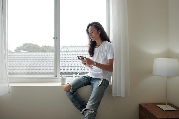 Tevreden jonge vietnamese man met golvend haar die op de vensterbank zit en smartphone gebruikt terwijl hij 's ochtends koffie drinkt in het hotel of thuis