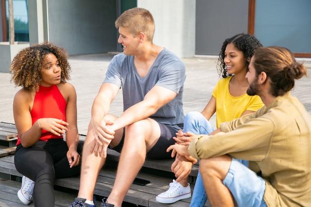 Tevreden jonge vrienden die in openlucht spreken