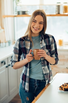 Tevreden jonge vrouw die thuis staat met een mok in haar handen