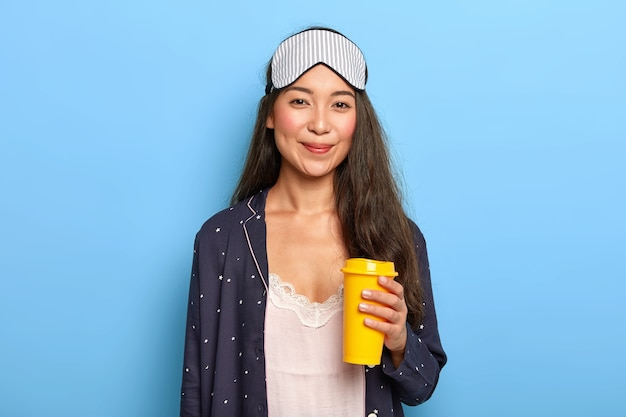 Tevreden jonge vrouw draagt slaapmasker en nachtkleding, probeert zich op te frissen met aromatische afhaalkoffie, geniet van rust