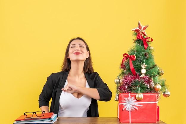 Tevreden jonge vrouw geniet van haar succes in pak in de buurt van versierde kerstboom op kantoor op geel