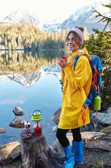 Tevreden jonge vrouw glimlacht zachtjes, warme drank drinkt, draagt regenjas en rubberen laarzen, geniet van zonnig weer na regen