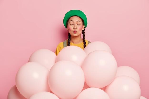 Tevreden jonge vrouw houdt lippen rond, draagt groene baret, heeft ogen dicht, heeft twee staartjes, staat in de buurt van heliumballonnen
