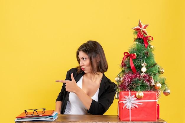 Tevreden jonge vrouw in pak dichtbij versierde kerstboom die iemand aan de rechterkant op kantoor op geel wijst