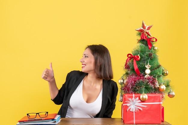 Tevreden jonge vrouw in pak in de buurt van versierde kerstboom ok gebaar maken op kantoor op geel